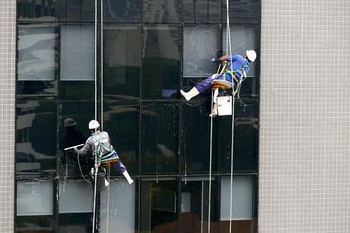 Trabalhadores limpando vidros de janelas de edifício