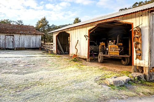 Trator em galpão de fazenda e grama congelada após geada