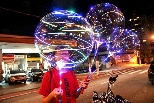 Adolescente vendendo brinquedo chinês em frente a restaurante à noite