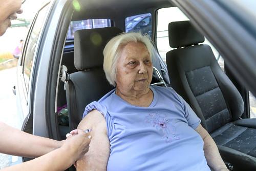 Idosa com dificuldade de locomoção recebendo vacina no veículo durante campanha anual de vacinação contra