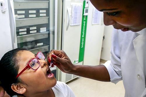Técnica de enfermagem aplica VOP Vacina Oral Poliomielite em menina no Dia D na UBS Unidade Básica de Saúde