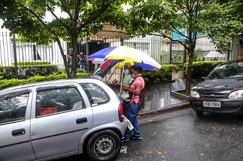 Vendedora ambulante de queijos e cliente pagando pelo produto - bairro Perdizes - uso de máscaras de proteç�
