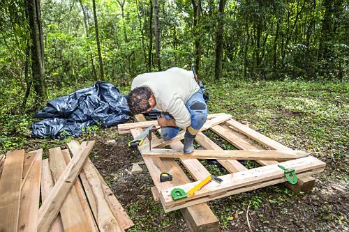 Homem construindo porteira de madeira