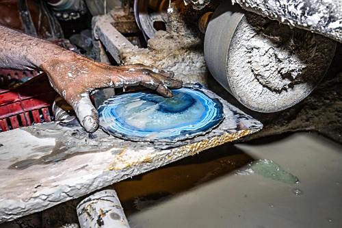 Detalhe de trabalhador polindo pedra ágata tingida artificialmente