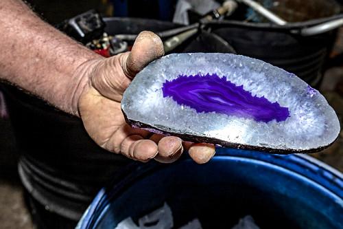 Detalhe de trabalhador exibe pedra ágata polida e tingida artificialmente