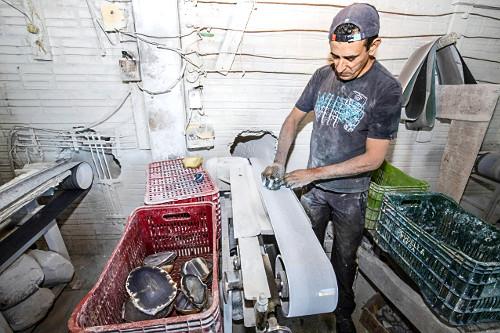 Trabalhador polindo pedras de ágata