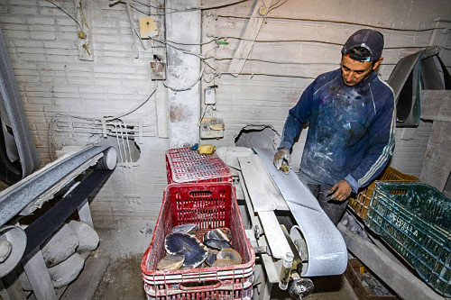 Trabalhador de empresa lixando pedras de ágata