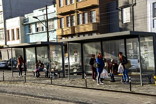Pessoas em ponto de ônibus no centro histórico