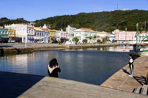 Pessoas no deck do Mercado Público - Lagoa do Imaruí e centro histórico ao fundo