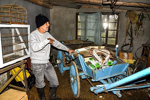 Sitiante mostrando carroça antiga de quatro rodas