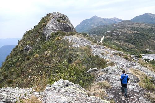 Vista de cima de guia caminhando em trilha na região do Pico das Agulhas Negras do Parque Nacional do Itatiai