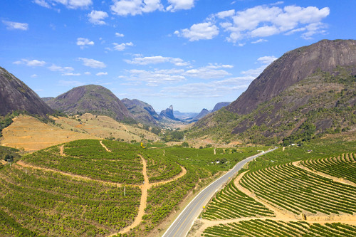 Vista de drone de plantação de café entre morros cortada pela rodovia ES-341 - ao fundo Morro do Camelo sí