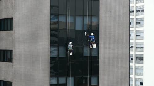Trabalhadores lavando vidros da fachada de edifício comercial